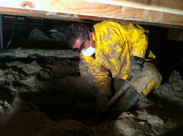 Construction Manager Joe digging a sump well in a muddy and wet subarea
